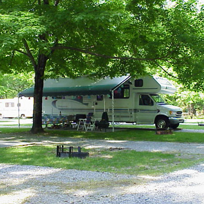A motorhome set up under a tree in one of our campgrounds