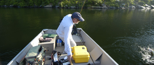 Byron Begley reaching for a landing net while fighting a smallmouth bass on June 11, 2013.