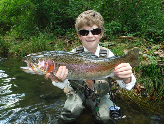 Tradd Little holding a large Arkansas rainbow trout.